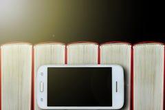 在书背景的智能手机  黑暗的背景,复制空间 概念:书和电子小配件 库存照片