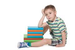 在书附近的哀伤的小男孩 库存图片