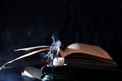 在书附近的被熄灭的蜡烛 库存照片
