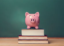 在书顶部的存钱罐与创造一教育费用题材的黑板 库存图片