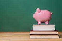 在书顶部的存钱罐与黑板 免版税库存图片