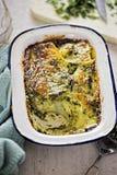 在乳脂状的调味汁的土豆和菠菜焦干酪 免版税图库摄影