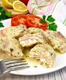 在乳脂状的调味汁的焖鱼用在板材的蕃茄 免版税图库摄影