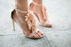 在乳脂状的颜色的典雅的鞋子-在妇女的腿的脚跟-花装饰 免版税库存图片