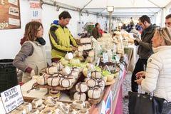 在乳酪供营商前面的游人蒙卡尔沃,意大利块菌市场的  图库摄影