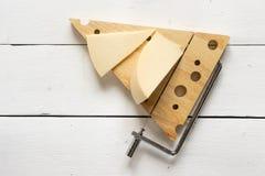 在乳酪切削刀的乳酪反对一张白色木桌 库存照片