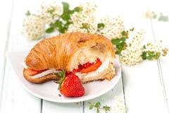 在乳酪和草莓中的新月形面包 库存照片