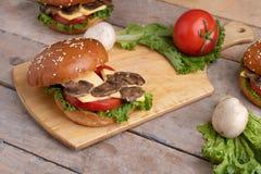 在乳酪和蕃茄的水多的油煎的蘑菇谎言 图库摄影