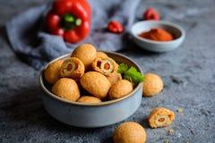 在乳酪和辣椒粉面团的被烘烤的橄榄 图库摄影