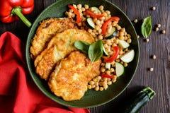在乳酪和面包渣涂的烤猪肉炸肉排,服务用鹰嘴豆和菜 库存照片