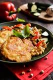 在乳酪和面包渣涂的烤猪肉炸肉排,服务用鹰嘴豆和菜 免版税图库摄影