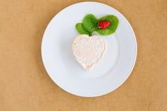在乳酪的草莓以在一块白色板材的心脏的形式 免版税库存照片