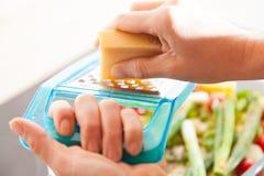 在乳酪磨丝器的手 免版税库存照片