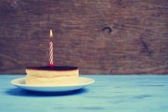 在乳酪蛋糕的被点燃的生日蜡烛,与一个减速火箭的作用 免版税库存图片