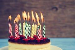 在乳酪蛋糕的被点燃的生日蜡烛,与一个减速火箭的作用 库存图片