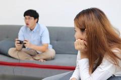 在争论的不快乐的恼怒的亚裔妇女与男朋友以后在客厅 坏关系夫妇概念 免版税库存图片