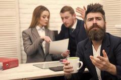 在事务的分歧 有胡子的人在有希望的面孔拿着杯子,上司,工友,背景的同事 库存照片