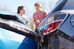 在事故以后的两个司机交换保险细节 免版税库存照片