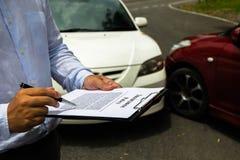 在事故以后的保险代理公司审查的汽车在路 在 图库摄影
