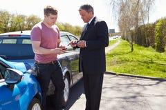 在事故以后的两个司机交换保险细节 免版税图库摄影