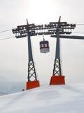 在二座滑雪电缆车定向塔之间的长平底船 免版税库存照片