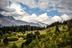 在云彩、山和领域的绿色风景在欧洲乡下 免版税库存照片