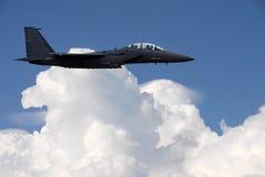 在云彩上的军事喷气机飞行 库存照片