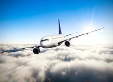 在云彩上的商业喷气机飞行 免版税库存照片