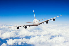 在云彩上的商业喷气机飞行 库存照片
