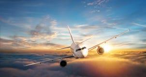 在云彩上的商业飞机喷气式飞机飞行在美丽的su 免版税库存图片