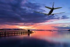在云彩上的商业飞机飞行与剧烈的日落或 库存照片