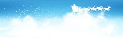 在云彩上的圣诞老人飞行与驯鹿雪撬 免版税库存照片