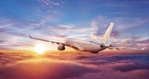 在云彩上的大商业飞机飞行在日落 免版税库存图片
