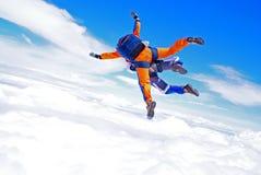 在云彩上的尽量延缓张伞的跳伞运动一前一后 库存图片