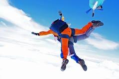 在云彩上的尽量延缓张伞的跳伞运动一前一后 免版税库存图片