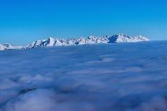 在云彩上的山上升 图库摄影