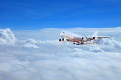 在云彩上的巨大的商业飞机飞行在剧烈的日落 免版税库存照片