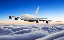 在云彩上的巨大的飞机飞行在剧烈的日落 库存图片