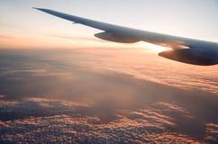 在云彩上的平面翼在日出, sunglight通过平面翼发出光线可看见 免版税图库摄影