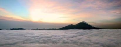 在云彩上的日出有山火山视图 免版税库存照片