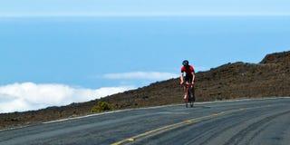 在云彩上的自行车车手 图库摄影
