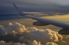 在云彩上的飞机飞行反对美好的日落 免版税库存图片