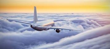 在云彩上的飞机飞行在剧烈的日落 免版税库存照片