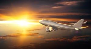 在云彩上的飞机飞行在日落期间 免版税库存照片