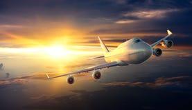 在云彩上的飞机飞行在日落期间 库存照片