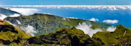 在云彩上的绿色山 免版税库存照片