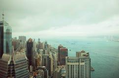 在云彩下的摩天大楼在维多利亚港附近水在雨前的 免版税库存照片