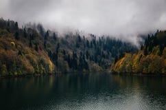 在云彩下的Autumn有雾的湖岸在黄昏 图库摄影