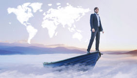 在云彩世界地图下的年轻经理 图库摄影