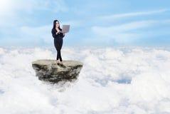 在云彩之上的女实业家和膝上型计算机 免版税库存照片